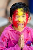 Cute Little Indian boy child welcome namste pose with coloured face during holi indian festival looking at camera stock photo