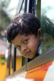 Cute little indian school kid looking from a bus Stock Photography