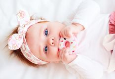 Cute little baby girl nibble a silicone doughnut teether. Cute little infant baby girl nibble a silicone doughnut teether royalty free stock photo