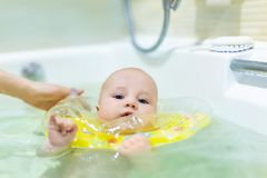 Cute little infant boy swimming with inflatable neck swim ring in bath. Baby having fun during water hygienic activities. Child stock images