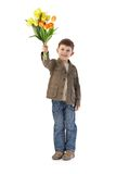 Cute little kid with bouquet of tulips smiling Stock Photos