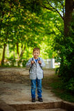Cute little kid boy with backpack on green nature background. Back to school concept Stock Photo