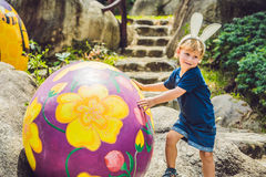 Cute little kid boy with bunny ears having fun with traditional Easter eggs hunt, outdoors. Celebrating Easter holiday. Toddler fi Royalty Free Stock Photo