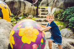 Cute little kid boy with bunny ears having fun with traditional Easter eggs hunt, outdoors. Celebrating Easter holiday. Toddler fi. Nding, colorful eggs Royalty Free Stock Images