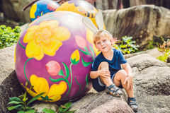 Cute little kid boy with bunny ears having fun with traditional Easter eggs hunt, outdoors. Celebrating Easter holiday. Toddler fi Stock Photography