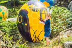 Cute little kid boy with bunny ears having fun with traditional Easter eggs hunt, outdoors. Celebrating Easter holiday. Toddler fi Stock Images