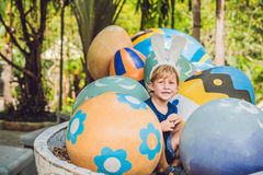 Cute little kid boy with bunny ears having fun with traditional Easter eggs hunt, outdoors. Celebrating Easter holiday. Toddler fi stock image