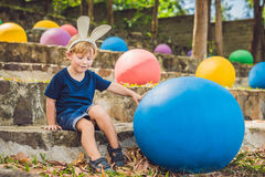 Cute little kid boy with bunny ears having fun with traditional Easter eggs hunt, outdoors. Celebrating Easter holiday. Toddler fi Stock Photos