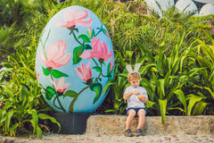Cute little kid boy with bunny ears having fun with traditional Easter eggs hunt, outdoors. Celebrating Easter holiday. Toddler fi Royalty Free Stock Photos