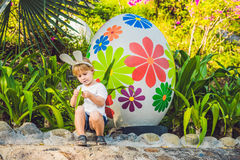 Cute little kid boy with bunny ears having fun with traditional Easter eggs hunt, outdoors. Celebrating Easter holiday. Toddler fi Royalty Free Stock Images