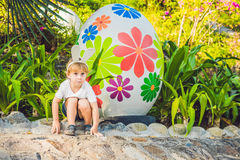 Cute little kid boy with bunny ears having fun with traditional Easter eggs hunt, outdoors. Celebrating Easter holiday. Toddler fi Stock Photo