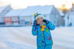 Little kid boy playing with snow in winter, outdoors. Cute little kid boy in colorful winter clothes having fun, outdoors during snowfall. Active outdoors Stock Photo
