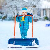 Little kid boy playing with snow in winter, outdoors. Cute little kid boy in colorful winter clothes having fun with snow shovel, outdoors during snowfall Stock Photos