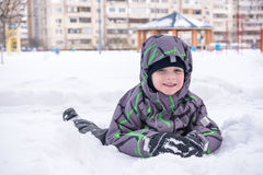 Cute little kid boy in colorful winter clothes laying down on . Active outdoors leisure with children in . Happy child. Stock Photos