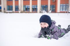 Cute little kid boy in colorful winter clothes laying down on . Royalty Free Stock Image