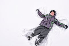 Cute little kid boy in colorful winter clothes making snow angel. Laying down on snow. Active outdoors leisure with children in winter. Happy child Stock Photos