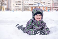 Cute little kid boy in colorful winter clothes making snow angel. Laying down on snow. Active outdoors leisure with children in winter. Happy child Stock Image