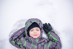 Cute little kid boy in colorful winter clothes making snow angel. Laying down on snow. Active outdoors leisure with children in winter. Happy child Royalty Free Stock Image