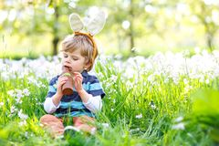 Cute little kid boy with Easter bunny ears celebrating traditional feast. Happy child eating chocolate rabbit fugure. On warm sunny day. Family, holiday, spring stock images