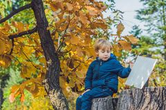 Cute little kid boy enjoying autumn day. Preschool child in colo. Rful autumnal clothes learning to climb, having fun in garden or park on warm sunny day Royalty Free Stock Photo