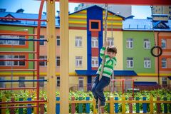 Cute little kid boy enjoying climbing rope on a playground. Toddler child learning to climb, having fun on warm sunny spring day. Active leisure with kids royalty free stock image