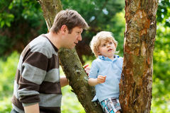 Cute little kid boy enjoying climbing on tree with father, outdo Stock Photography