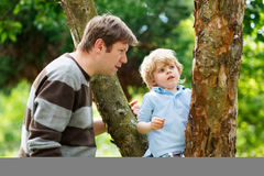 Cute little kid boy enjoying climbing on tree with father, outdo Stock Photos