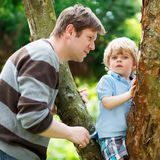 Cute little kid boy enjoying climbing on tree with father, outdo Stock Photo