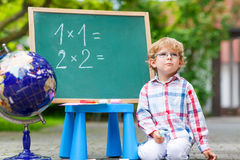 Cute little kid boy with glasses at blackboard practicing mathem Stock Photos
