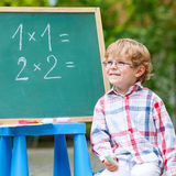 Cute little kid boy with glasses at blackboard practicing mathem Royalty Free Stock Images