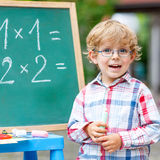 Cute little kid boy with glasses at blackboard practicing mathem Royalty Free Stock Photo