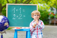 Cute little kid boy with glasses at blackboard practicing mathem Stock Image