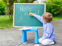 Cute little kid boy with glasses at blackboard practicing writin Royalty Free Stock Images