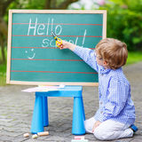 Cute little kid boy with glasses at blackboard practicing writin Stock Photography