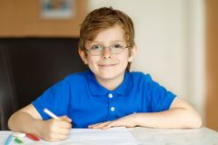 Cute little kid boy with glasses at home making homework, writing letters with colorful pens. Little child doing exercise, indoors. Elementary school and royalty free stock image