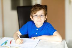 Cute little kid boy with glasses at home making homework, writing letters with colorful pens. Little child doing exercise, indoors. Elementary school and royalty free stock photography
