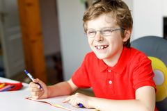 Cute little kid boy with glasses at home making homework, writing letters with colorful pens. Little child doing exercise, indoors. Elementary school and stock image