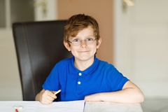 Cute little kid boy with glasses at home making homework, writing letters with colorful pens. Little child doing exercise, indoors. Elementary school and stock images