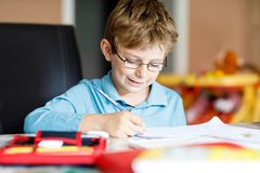Cute little kid boy with glasses at home making homework, writing letters and doing maths with colorful pens. Little. Cute little kid boy with glasses at home royalty free stock image