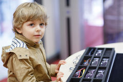 Cute little kid boy at optician store during choosing his new gl Royalty Free Stock Photography