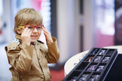 Cute little kid boy at optician store during choosing his new gl Royalty Free Stock Photos