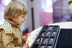 Cute little kid boy at optician store during choosing his new gl Stock Image