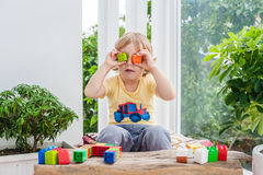 Cute little kid boy with playing with lots of colorful plastic blocks indoor. Active child having fun with building and. Creating of tower. Promotion of skills Stock Photos