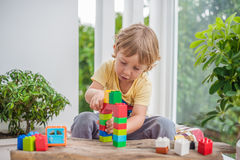 Cute little kid boy with playing with lots of colorful plastic blocks indoor. Active child having fun with building and. Creating of tower. Promotion of skills Royalty Free Stock Photos