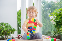 Cute little kid boy with playing with lots of colorful plastic blocks indoor. Active child having fun with building and. Creating of tower. Promotion of skills Stock Image