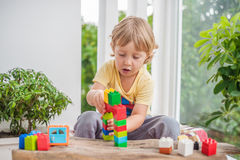 Cute little kid boy with playing with lots of colorful plastic blocks indoor. Active child having fun with building and. Creating of tower. Promotion of skills Royalty Free Stock Photo