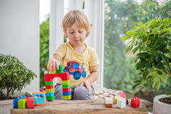 Cute little kid boy with playing with lots of colorful plastic blocks indoor. Active child having fun with building and. Creating of tower. Promotion of skills Royalty Free Stock Images