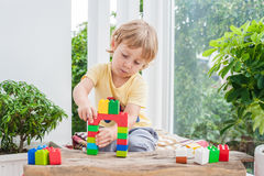 Cute little kid boy with playing with lots of colorful plastic blocks indoor. Active child having fun with building and. Creating of tower. Promotion of skills Royalty Free Stock Image