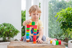 Cute little kid boy with playing with lots of colorful plastic blocks indoor. Active child having fun with building and creating o. F tower. Promotion of skills Royalty Free Stock Photography