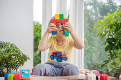 Cute little kid boy with playing with lots of colorful plastic blocks indoor. Active child having fun with building and creating o Stock Image